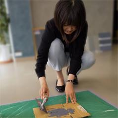 画像:塗料をダンボールに広げる女性
