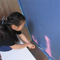 画像:ピンクの壁を青く塗る子ども