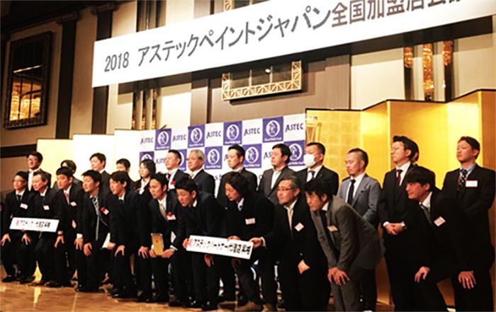 (株)アステックジャパンの塗料実績、新潟県第一位で表彰され、記念写真を撮る満永社長