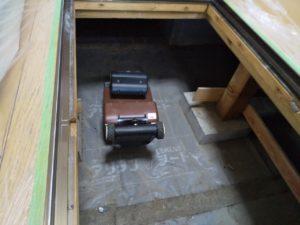 床下の点検口に置かれたロボットの写真