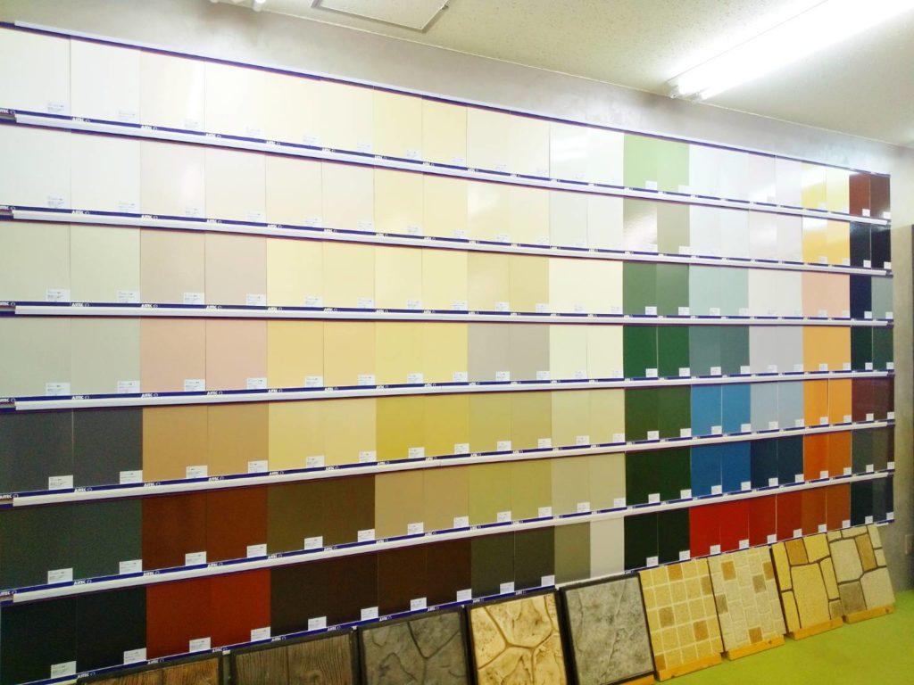 室内の壁に塗料の色見本が並べられている写真