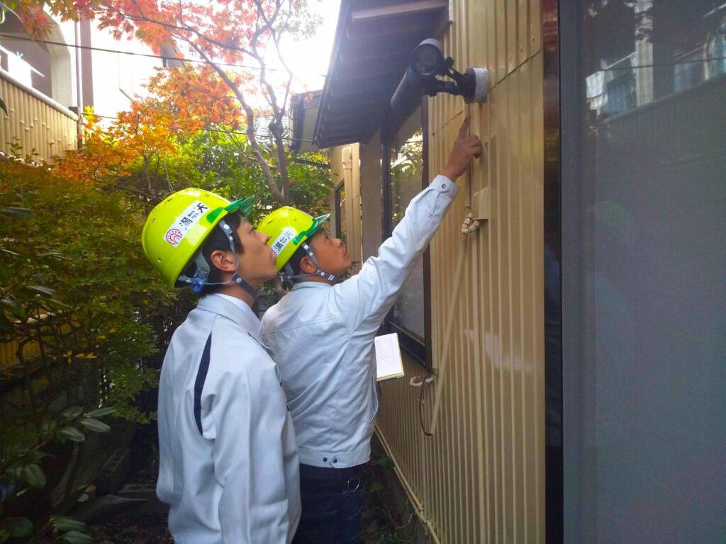 写真:建物の調査方法を先輩社員が部下へ指導している