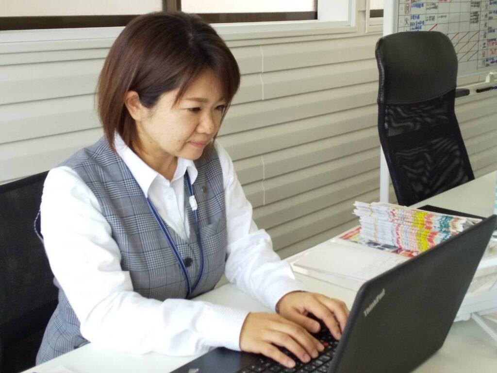 写真:パソコンに向かいデスクワークを行っている